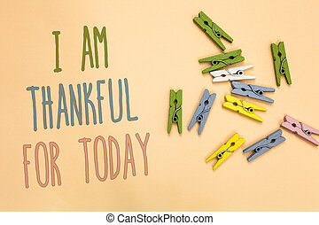 Text sign showing I Am Thankful For Today. Conceptual photo Grateful about living one more day Philosophy Yellow base with painted texts colorful paper clips laid randomly on ground.