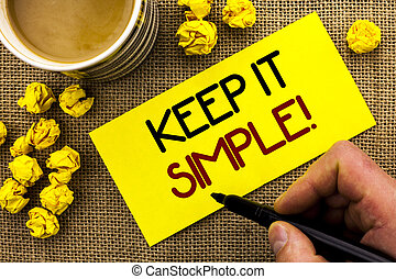 Text sign showing Keep It Simple Motivational Call. Conceptual photo Simplify Things Easy Clear Concise Ideas written on Sticky Note Paper on the jute background Cup and Paper Balls next to it.