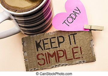 Text sign showing Keep It Simple Motivational Call. Conceptual photo Simplify Things Easy Clear Concise Ideas written on Tear Cardboard Piece on the plain background Pink Heart and Coffee Cup.