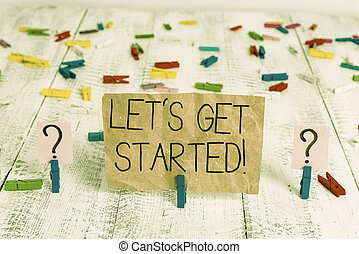 Text sign showing Let S Get Started. Conceptual photo encouraging someone to begin doing something Scribbled and crumbling sheet with paper clips placed on the wooden table.