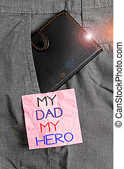 Text sign showing My Dad My Hero. Conceptual photo Admiration for your father love feelings emotions compliment Small little wallet inside man trousers front pocket near notation paper.