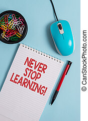 Text sign showing Never Stop Learning. Business photo text keep on studying gaining new knowledge or materials Notebook and writing equipment with computer mouse above pastel backdrop