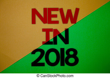 Text sign showing New In 2018. Conceptual photo upcoming year resolution Advertising new product Specs Yellow green split background message thoughts important information.