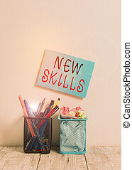Text sign showing New Skills. Conceptual photo Recently Acquired Learned Abilities Knowledge Competences Blue Sticky Card on Wall Two Pencil Pots Pens Pencils Markers Waste Paper.