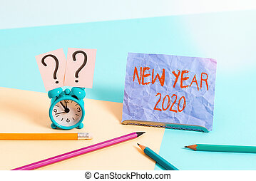 Text sign showing New Year 2020. Conceptual photo Greeting Celebrating Holiday Fresh Start Best wishes Mini size alarm clock beside stationary placed tilted on pastel backdrop.