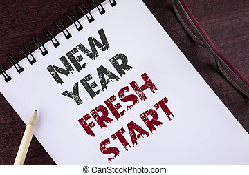 Text sign showing New Year Fresh Start. Conceptual photo Time to follow resolutions reach out dream job written on Notepad on the Wooden background Pencil and Glasses next to it.