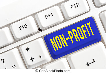 Text sign showing Non Profit. Conceptual photo providing products or service without paying back in return White pc keyboard with empty note paper above white background key copy space.