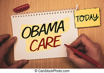 Text sign showing Obama Care. Conceptual photos Government Program of Insurance System Patient ProtectionMan creating for today on notebook Hand hold holding pen Wooden background.