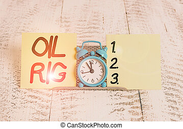Text sign showing Oil Rig. Conceptual photo large structure with equipment to remove oil from under the seabed Mini blue alarm clock standing above buffer wire between two notation paper.