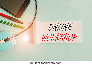 Text sign showing Online Workshop. Business photo showcasing intensive discussion and activity on a particular subject Notebook and writing equipment with modern gadget above pastel backdrop