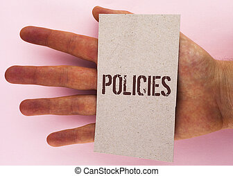 Text sign showing Policies. Conceptual photo Business Company or Government Rules Regulations Standards written on Cardboard Piece placed on Hand on the plain background.