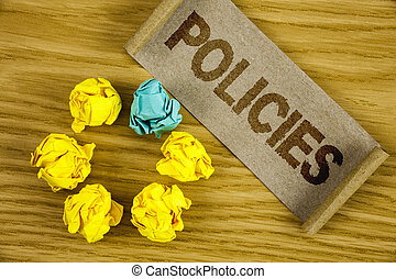Text sign showing Policies. Conceptual photo Business Company or Government Rules Regulations Standards written on Folded Cardboard Paper piece on wooden background Crumpled Paper Balls.