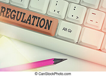 Text sign showing Regulation. Conceptual photo the authoritative rule dealing with details or procedure Different colored keyboard key with accessories arranged on empty copy space.