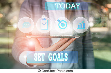 Text sign showing Set Goals. Conceptual photo Defining or achieving something in the future based on plan Female human wear formal work suit presenting presentation use smart device.