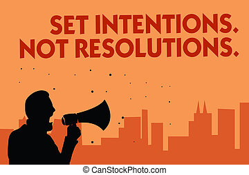 Text sign showing Set Intentions. Not Resolutions.. Conceptual photo Positive choices for new start achieve goals Man holding megaphone speaking politician making promises orange background.