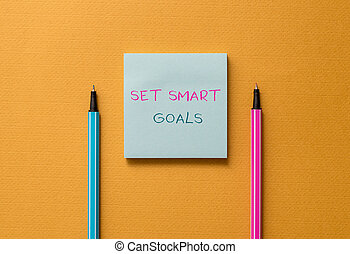 Text sign showing Set Smart Goals. Conceptual photo giving criteria to guide in the setting of objectives Front view blank colored sticky note two ballpoints cool yolk background.