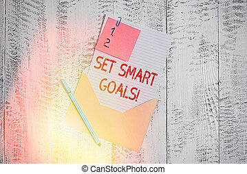 Text sign showing Set Smart Goals. Conceptual photo giving criteria to guide in the setting of objectives Envelope blank sheet letter paper sticky note ballpoint wooden background.