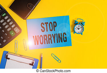 Text sign showing Stop Worrying. Business photo showcasing stop thinking about something bad that happened in the past Clipboard clips sheet calculator pencil alarm clock wallet color background