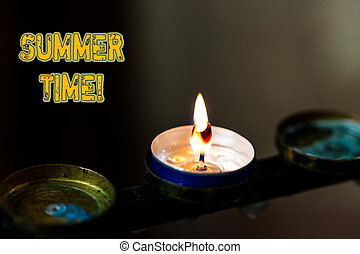 Text sign showing Summer Time. Conceptual photo achieve longer evening daylight summer setting clocks hour ahead Abstract burning candle set of three just one shining flame glowing dark.