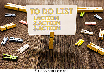 Text sign showing To Do List 1.Action 2.Action 3.Action. Conceptual photo putting day priorities in order Clothespin holding white paper note several clothespins wooden floor.