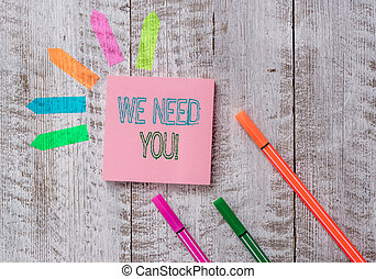 Text sign showing We Need You. Conceptual photo asking someone to work together for certain job or target Plain note paper and line arrow stickers on the top of wooden table desk.