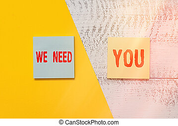 Text sign showing We Need You. Conceptual photo asking someone to work together for certain job or target Two multicolor blank notepads colored paper sheet retro wooden background.