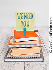 Text sign showing We Need You. Conceptual photo asking someone to work together for certain job or target pile stacked books notebook pin clothespin colored reminder white wooden.