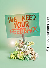 Text sign showing We Need Your Feedback. Conceptual photo Give us your review thoughts comments what to improve Reminder pile colored crumpled paper clothespin reminder blue background.