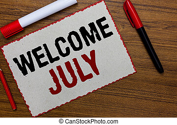Text sign showing Welcome July. Conceptual photo Calendar Seventh Month 31days Third Quarter New Season White paper red borders markers wooden background communicating ideas.