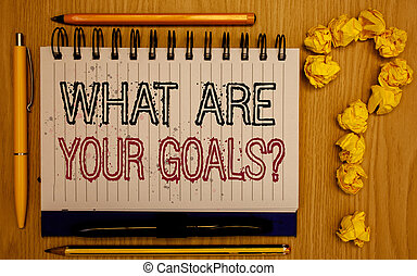 Text sign showing What Are Your Goals Question. Conceptual photo asking someone about his life targets Notepad with outline text pen pencil woody desk crimp balls form query mark.