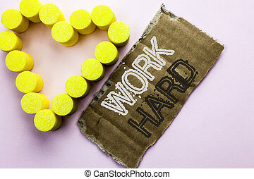 Text sign showing Work Hard. Conceptual photo Struggle Success Effort Ambition Motivation Achievement Action written on Tear Cardboard Piece on the plain background with Heart next to it.
