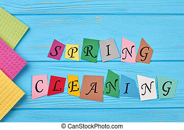 Text spring cleaning on wooden background.