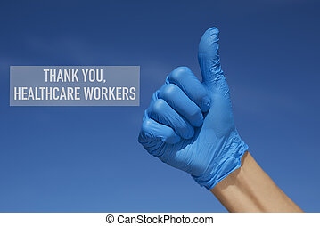 closeup of the hand of a man, wearing blue surgical gloves, giving a thumb sign and the text thank you healthcare workers against the blue sky