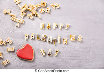 Text Valentines day written with macaroni in the form of letters and red heart cookie on grey wooden table background