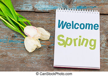 Text Welcome Spring on notebook. Fresh flowers on old wooden background