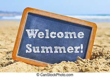 text welcome summer in a chalkboard, on the sand of a beach