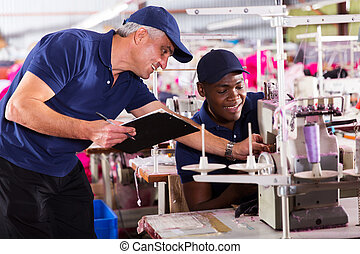 textile factory foreman helping machinist with sewing...
