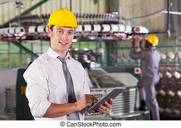textile factory manager using tablet computer - modern...