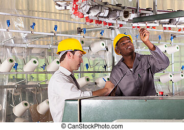 textile factory worker and quality controller checking...