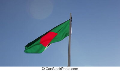 Textile flag of Bangladesh on a flagpole in front of blue...