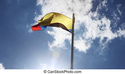 Textile flag of Colombia on a flagpole in front of blue sky