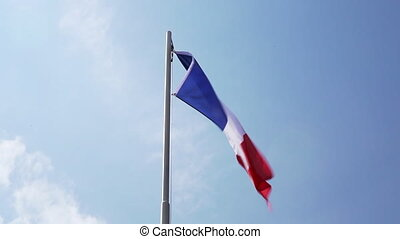 Textile flag of France on a flagpole in front of blue sky