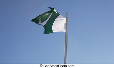 Textile flag of Pakistan on a flagpole in front of blue sky