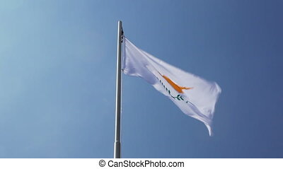 Textile flag of Spain on a flagpole in front of blue sky