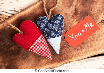 Textile hearts on wooden surface.