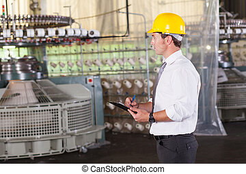 textile prodcution manager working inside factory