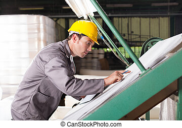 textile quality controller checking fabrics on QC table