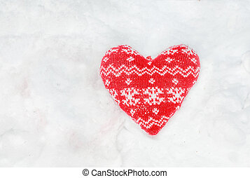 Textile red heart with snow flakes on the snow