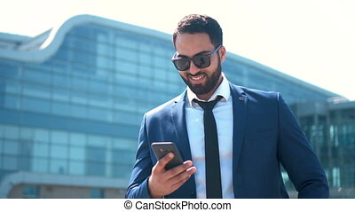 Texting by Phone - Handsome bearded businessman wears blue...