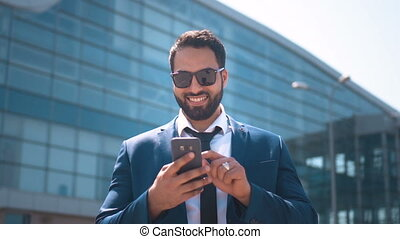 Texting by Phone - Sexy bearded businessman wears blue suit...